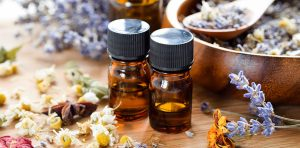Two bottles of essential oils for cancer sit on a table with dried herbs