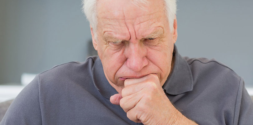 A man is coughing, a known symptom of mesothelioma
