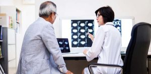 A doctor and her patient are looking at MRI brain scans