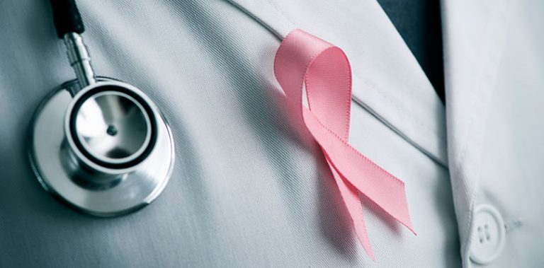 A medical professional is wearing a breast cancer ribbon
