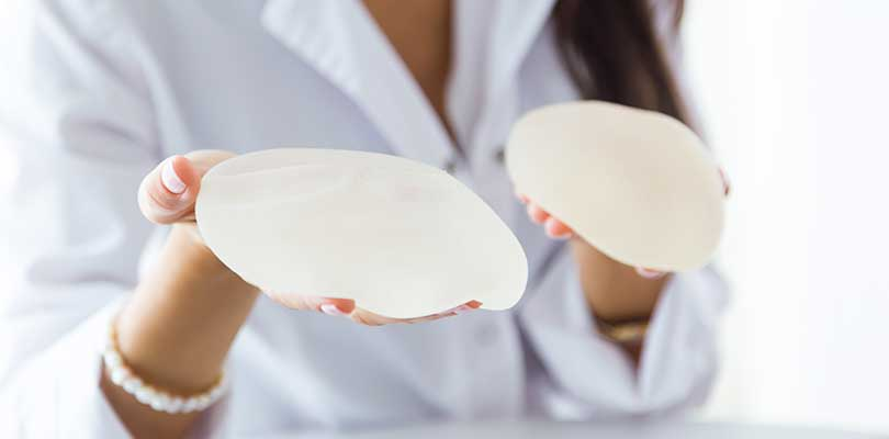 A doctor holding two silicon implants for a breast reconstruction surgery