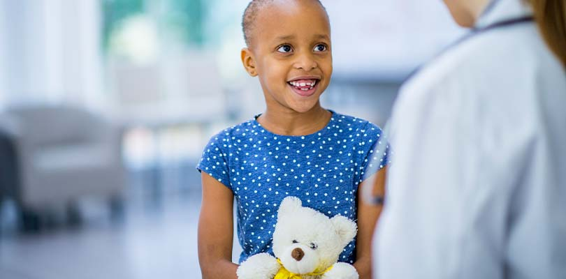 A little girl holding a teddy bear while talking to a doctor.